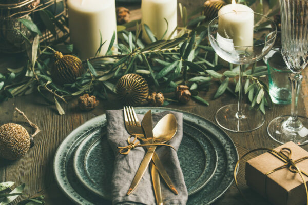 Christmas or New Years party table setting. Plates, golden cutlery, glasses, gift box, festive branch decoration, candles, gliterring toys over wooden table background, selective focus, square crop
